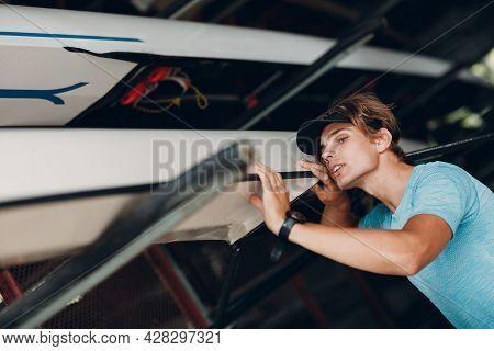 Sportsman Single Scull Man Rower Sportsman Cheking Carbon Surface Of Boat.