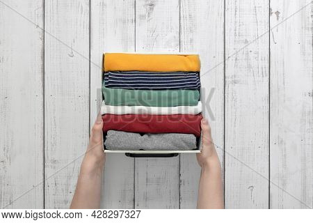 Hands Hold A Container With Neatly Folded Clothes, Storage Of Things, Putting Things In Order In The
