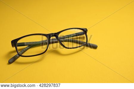Children's Glasses Lie On A Yellow Close-up With Space For Text. Mines Space. The Concept Of Childre