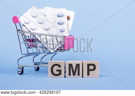 The Word Gmp - Abbreviation Of Good Manufacturing Practice On Wooden Cubes, On A Blue Background Wit