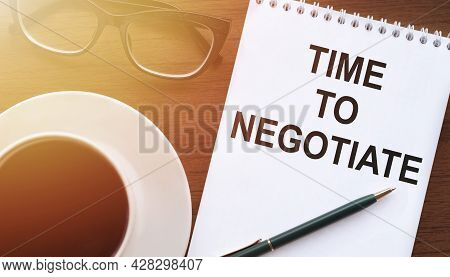 Time To Negotiate - Text On Paper With Cup Of Coffee And Glasses On Wooden Background In Sinlight.