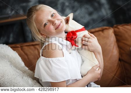 Mother and daughter relationship concept. A woman congratulates happy teenage girl on her birthday and gives her a gift. A dog in box. The family celebrates anniversary at home