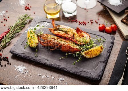 Lobster with flavored butter. Herb butter, lemon. Delicious healthy traditional food closeup served for lunch in modern gourmet cuisine restaurant.
