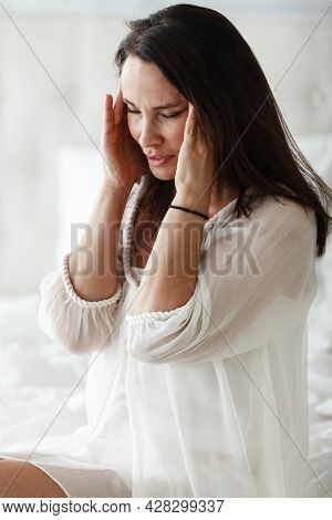 Middle aged woman sitting on a white bed in a bedroom at home touching her head with her hands while having a headache pain and feeling unwell. Suffering from insomnia or migraine.