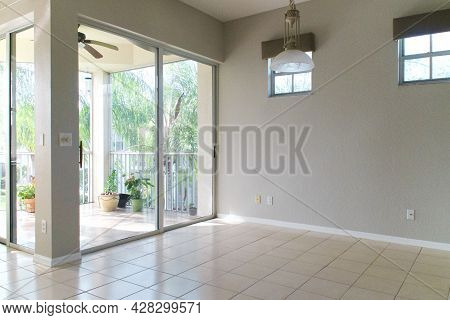 View Of An Empty Neutral Colored Room With High Windows And Sliding Glass Doors To Balcony