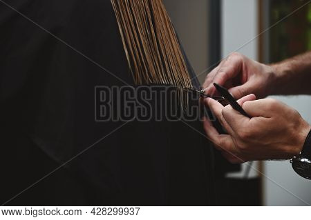 A Close-up Of Hairdresser's Hands Cutting Hair. Master Of Hairstyles Cutting Woman's Hair In Beauty