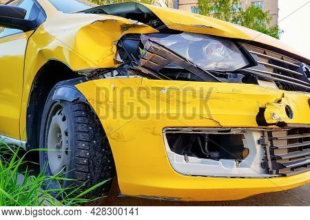 Close-up And Selective Focus Of A Badly Broken Yellow Taxi Car With Torn, Crumpled And Scratched Par