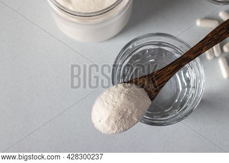 Collagen Powder In Spoon On Glass Of Water, Collagen Capsules On Light Background, Healthy And Antia