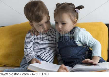 Two Preshool, Toddler Children Read Large Interesting Book Of Fairy Tales On Yellow Bed. Siblings Li