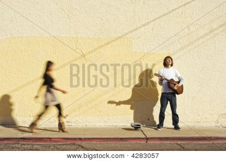 Musician On Sidewalk And Woman Pedestrian