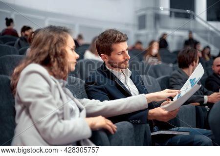 Business Seminar Participants Discuss Financial Schedules. Rear View.