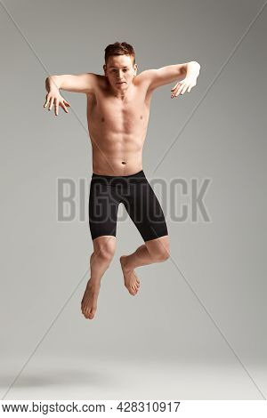 Swimmer In A Jump On A Gray Background, Swimming Concept, Spear Space, Athlete In Swimming Trunks Fo
