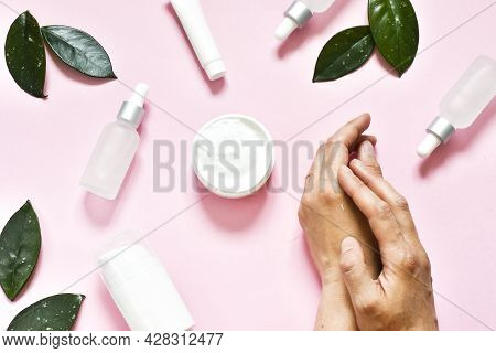 Cosmetic Cream On Female Hands, Jars With Milk Swirl Cream And Green Leaves On A Pink Background. Fl