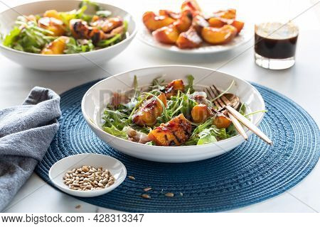 Grilled Peach And Arugula Salad With More Peaches In Behind Against A Bright Sunny Window.