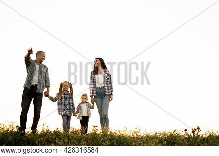 Happy Family Dad Mom And Daughters Walk In Nature In The Field In The Summer At Sunset. Parents With