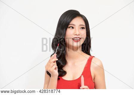 Beautiful Young Woman Doing Makeup Using A Lip Gloss