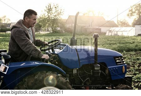 Farmer Driving A Tractor Across The Field. Agro Industry, Agribusiness. Farming, Agriculture. Countr