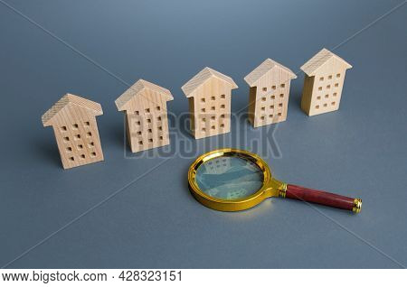 Residential Apartment Buildings And A Magnifying Glass. Apartment Search Concept. Buying Or Renting