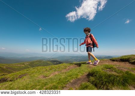 Trekking In The Mountains With A Child, Boy With A Backpack Walks Along A Mountain Trail, Outdoor Re