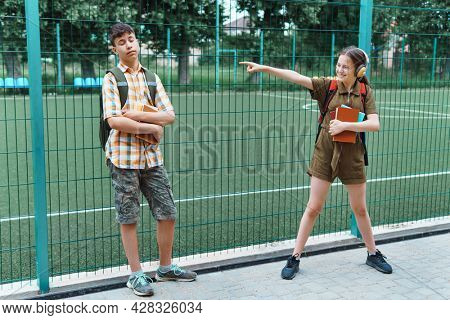 two teenagers boy and girl playing on the way to the school, education and back to school concept