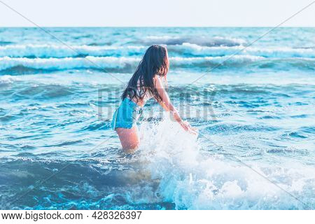Young Woman Playing In The Sea In Summer. Woman Make In Sea Water Splash.cheerful Young Woman Having