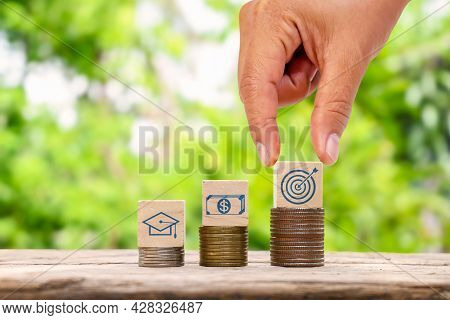 Hand Holding Wooden Cube With Virtual Goals On The Stack Of Coins And Business Success Goals Objecti