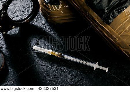 Heroin In A Syringe On The Dark Cement Floor. An Addictive Substance, A Drug, An Illegal Thing, The