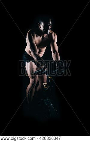 Strong Man Using The Static Bike With Black Background