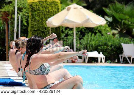 Women In Bikini Doing Aqua Aerobics Sitting In A Row On The Swimming Pool Edge. Water Sport, Vacatio