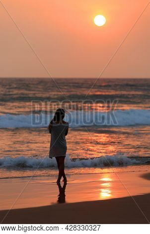 Abstract girl figure on sea sunset bacground