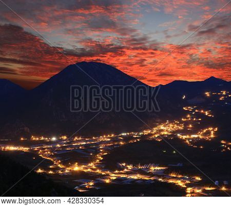 night landscape with lights in the village at the foot of the mountains. Take in Turkey mountains