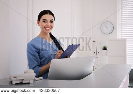 Receptionist With Clipboard At Countertop In Hospital