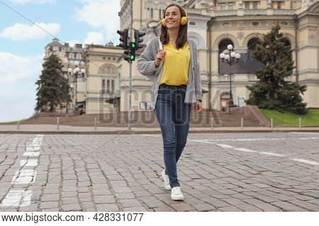 Young Woman With Headphones Crossing Street. Traffic Rules And Regulations