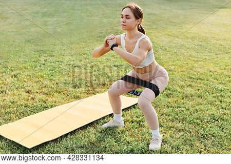 Full Length Of Young Sporty Fit Woman In Modern Sportive Clothes Exercising With Resistance Band Squ
