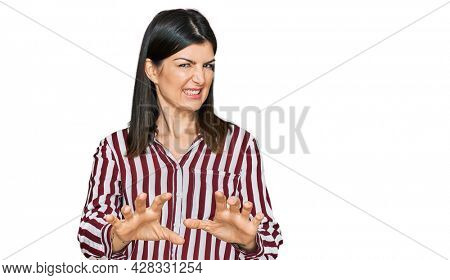 Beautiful brunette woman wearing striped shirt disgusted expression, displeased and fearful doing disgust face because aversion reaction. with hands raised