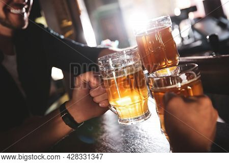 Friends Clinking Glasses With Beer In Pub, Closeup