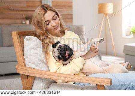 Woman With Cute Pug Dog At Home. Animal Adoption