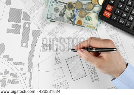 Cartographer With Calculator And Money Drawing Cadastral Map, Closeup