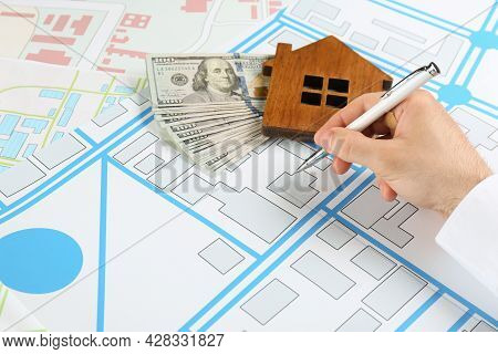Cartographer With House Model And Money Drawing Cadastral Map, Closeup