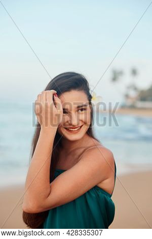 Woman With Beauty Face Touching Skin . Beautiful Smiling Girl Model On The Beach. Young Smiling Woma