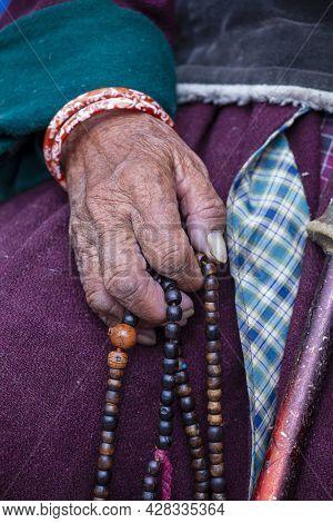 Old Tibetan Woman Holding Buddhist Rosary In Hemis Monastery, Ladakh, Jammu And Kashmir State, North