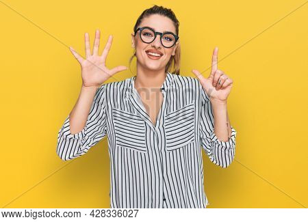 Young caucasian woman wearing business shirt and glasses showing and pointing up with fingers number seven while smiling confident and happy.