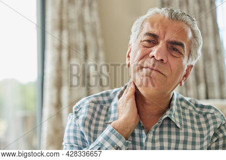 Mature Man At Home Suffering From Muscle Pain Or Ache In Neck