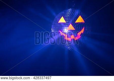 Halloween party pumpkin disco ball, jack o'lantern with shiny blue rays in smoke