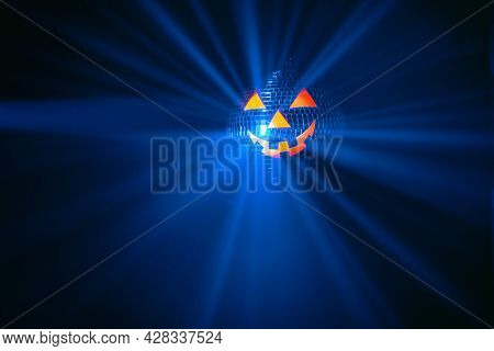 Halloween party pumpkin disco ball, blue shiny rays background with copy-space