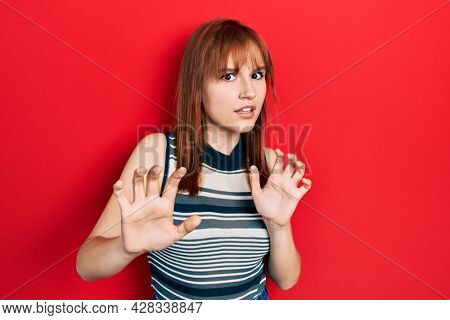 Redhead young woman wearing casual t shirt disgusted expression, displeased and fearful doing disgust face because aversion reaction. with hands raised