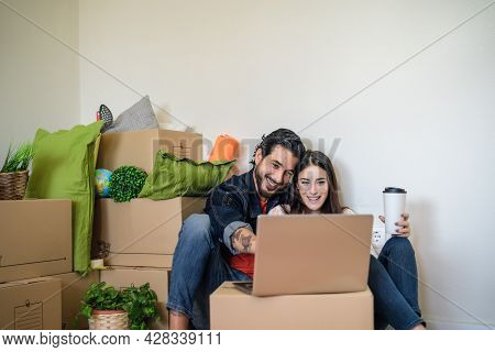 Happy Young Couple Moving In New Property House While Using Laptop For Shopping Online