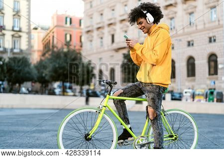Happy African Man Using Mobile Smartphone Outdoor - Young Guy Having Fun Riding With Bike In The Cit