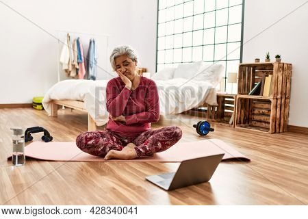 Middle age woman with grey hair training at home looking at exercise video on laptop thinking looking tired and bored with depression problems with crossed arms.