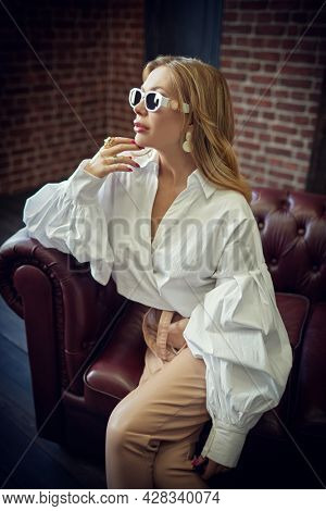 Glamorous middle-aged woman with enlarged full lips poses in fashionable clothes and sunglasses on a leather sofa. Luxury lifestyle. High fashion shot.